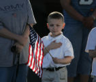 JPM844 Jon-Michael Ferrell, 6, covers his heart with his hand and waves an American flag as he...