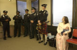 far right of frame only, Deputy Jeremy Heinrich, kilts and bagpipes, prepares to play while the...
