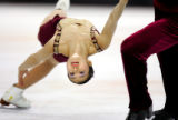 American figure skater Rena Inoue (left) gets spun in a circle by her skating partner John Baldwin...