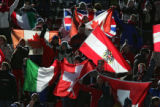 Fans from a number of nations proudly display their falgs as they cheer for their skiiers during...