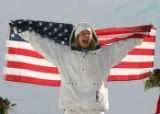 Hannah Teter celebrates while holding the U.S. flag after winning the gold medal in women's...