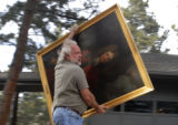 Larry Barber(cq), runs with a painting in a rush to evacuate himself and valuables from his home...