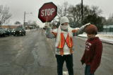 Crossing guard for Poudre School Distict Denise Carey (cq) (l) stops traffic for Colton Fisher, 9...
