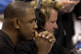 Kyle Speller (cq), game announcer for the Denver Nuggets, says a prayer before the start of the...