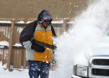 Bill Hagler (cq) uses a blower to clear snow off the cars at Kelley's Used Cars, 9220 West Colfax,...