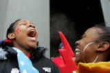 Manual High School students Oshanette Lewis, cq, left, and  Chanel Johnson, cq, cheer outside the...