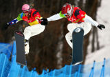 U.S. snowboarder Lindsey Jacobellis (right, #3) goes over a jump mid-course with French rider...