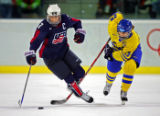 U.S. Women's Hockey Team captain Krissy Wendell (#7, F) gets tripped up by Sweden's Danijela...