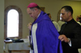 Bishop Bernard Fellay  (left) is helped with his vesting by Father Christopher Pieroni (right)...