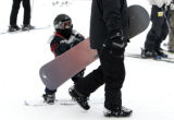 Snow boarder Jimmy Ramirez the 3rd,4 years old,  hitches a ride from his snow boarder dad Jim...