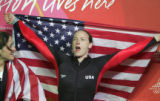 Shauna Rohbock, right, yells while holding the U.S. flag after she and brakeman Valerie Fleming,...