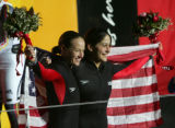 Pilot Shauna Rohbock, left, and brakeman Valerie Fleming, right, hold a U.S. flag and celebrate...