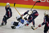 U.S. Women's Hockey Team member Jamie Hagerman (#11) takes down Finland's Satu Kiipeli (#5) during...
