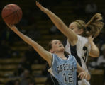 Greeley West's Amanda Schweers, left, goes up for a shot being defended by Mullen's Bianca Holley,...