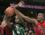 Colorado State guard Cory Lewis, middle, is smothered by San Diego State defenders Mohamed Abukar,...