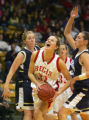 Aija Putnina (#33), of Regis, center, tries to fight her way through Carrie Wagner (#31), left,...