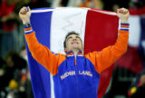Gold medalist Bob de Jong of the Netherlands savors the moment as he runs a victory lap with his...