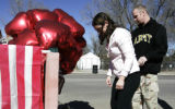 Denise and Dave Calhoun (cq) (l-r) placed a flag and a flower on a memorial.  They felt a need to...