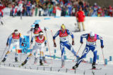 Giorgio di Centa, of Italy, leads a group of skiers as they race towards the finish of the men's...