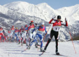 Mikhail Botwinov, of Austria, leads a group of skiers with the Italian Alps in the background in...