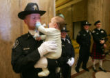 Brandon Blum (cq), 5 months, grabs the nose of his father Deputy Sheriff Kurt Blum (cq), during a...