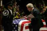 Thomas Jensen pats the coffin of his son Jared Jensen as he prepares to kiss him good bye.  In...