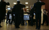 Behind the coffin of her husband, police officer Jared Jensen, Natalie Jensen (far rt) cradles the...