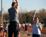 Pole vaulting coach Bonnie Bell, (cq) right, instructs student Luke Biewick (cq), 15, a sophmore...