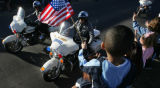 JPM1094 Jordan Hogan, 3, waves a flag as motorcycle officers from the El Paso County Sheriff's...