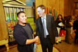 Seventeen year-old sophomore Christian Campos (cq, left) shakes hands with Denver Mayor John...