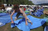 Telluride, CO. June 18th, 2004 Nash Emrich from Durango, frantically puts down his tarp on the...