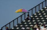 A fan uses an umbrella to get some shade at Hi Corbett Field March 2, 2006. The Rockies won their...