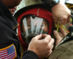 (DENVER, Colo., June 15, 2004)  Antoinette Torres-Janke gets help with her firefighting gear from...