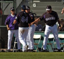 Colorado Rockies Ian Stewart (64) is congratulated by coaches Jamie Quirk, Duane Espy and manager...