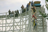 Rescue crews at Lakeside Amusement park help  passengers down the track of the Cyclone roller...