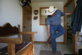 MJM520  Preparing for an afternoon horse ride, Tracy Ringolsby (cq), puts on his cowboy boots at...