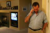 Mark Paschall talks on the phone as he gathered with friends at Susan Johnson's house in Arvada,...