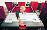 Election Official Samantha Shue (cq) adjusts a voting booth for a handicapped voter at the...