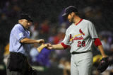 St. Louis Cardinals starting pitcher Chris Carpenter (#29) hands a wet chalk bag to home plate...