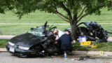 Police officers investigate the front half of an automobile at a fatal one vehicle car crash near...