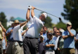 U.S. golfer Phil Mickelson hits out of the rough on his first hole while surrounded by a gallery...