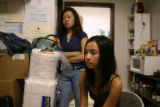 Older sister Yen Than (standing left), 28, and wife Emily Than, 25, talk about Quang Tony...