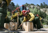 Aaron DiMartino(cq), 21, (foreground) readies water boxes for carrying up the hill (seen behind...