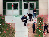 Investigators tackle the intricate task of marking evidence where gunmen entered the school.